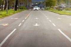 Pfeilzeichen und weißes Auto auf Straße Lizenzfreies Stockfoto