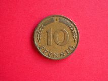 10 pfenning coin. Vintage 10 pfenning coin from Germany over red background stock photos