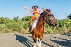 Pferd mit zwei kleinen Mädchen Reitim Sommer in Ada Bojana, Monte Lizenzfreie Stockfotos