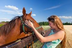 Pferd und blondes Mädchen in der Koppel auf Sommern Lizenzfreie Stockbilder