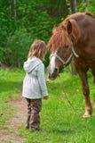 Pferd und kleines Mädchen. Stockbild