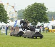 Pferd und Reiter über Hindernis Stockfotos