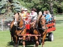 Pferdekutsche/Lastwagen mit Leuten Stockbild