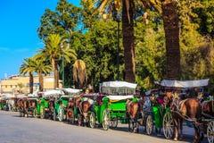 Pferdekutschen auf dem Hauptplatz in Marrakesch Stockbilder