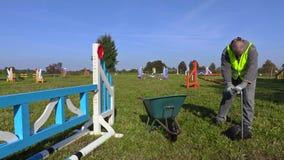 Pferdelenker sammelt Düngemittel auf Hürdenfeld stock video