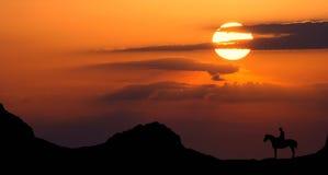 Pferdenmitfahrer im Sonnenuntergang Stockfotos