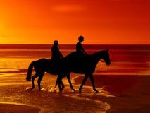 Pferdenreiten am Sonnenuntergang Lizenzfreie Stockfotos