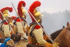 Pferdereiter, die goldene Sturzhelme mit roten Gefiedern tragen Stockbilder