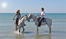 Pferderueckenreiten im Meer Stockfotos