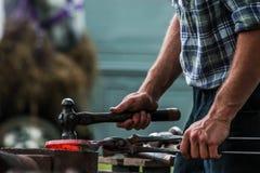 Pferdeschuh, der vom Schmied/vom Hufschmied in Handarbeit gemacht wird Lizenzfreie Stockfotos