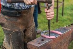 Pferdeschuh, der vom Schmied/vom Hufschmied in Handarbeit gemacht wird Lizenzfreies Stockbild