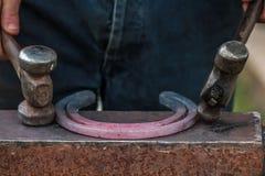 Pferdeschuh, der vom Schmied/vom Hufschmied in Handarbeit gemacht wird Stockfoto