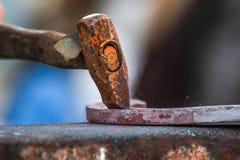 Pferdeschuh, der vom Schmied/vom Hufschmied in Handarbeit gemacht wird Stockfotos