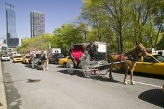 Pferdewagen fährt in Verkehr unten Central Park nach Westen in Manhattan, New York City, NY Stockfotografie