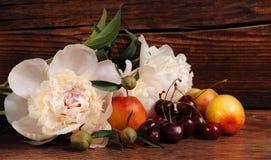 Pfingstrose, Kirsche und Pfirsich Stillleben mit frischen Beeren und Blumen Stockbilder