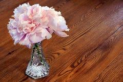 Pfingstroseblumen auf hölzerner Tabelle Stockfoto