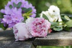 Pfingstrosen und Gartenblumen auf hölzernen Planken Stockfoto