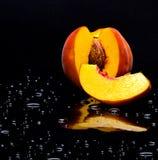 Pfirsich auf dem schwarzen Hintergrund mit Wasser Stockfotos