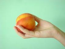 Pfirsich auf einem grünen Hintergrund in der Hand des Mädchens stockbilder