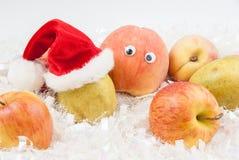 Pfirsich mit Augen und Birne mit Sankt-Hut Stockbild