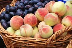 Pfirsich- und Pflaumegetreide in einem Korb Lizenzfreies Stockfoto