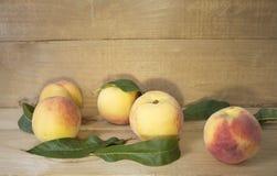 Pfirsiche auf einem braunen Hintergrund Pfirsiche mit grünen Blättern Ansicht von oben genanntem in den grünen Blättern Lizenzfreie Stockfotografie