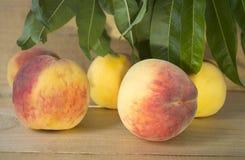 Pfirsiche auf einem braunen Hintergrund Pfirsiche mit grünen Blättern Ansicht von oben genanntem in den grünen Blättern Lizenzfreie Stockfotos