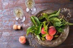 Pfirsiche auf Niederlassung mit Champagner Stockbilder