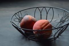 Pfirsiche im schwarzen Drahtkorb Stockfoto