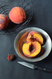 Pfirsiche im schwarzen Drahtkorb, halbierter Pfirsich in der Zinnschüssel Stockbilder