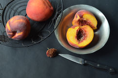 Pfirsiche im schwarzen Drahtkorb, halbierter Pfirsich in der Zinnschüssel Stockbild
