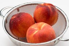 Pfirsiche mit Morgen befeuchten in einem Edelstahlsieb stockbild