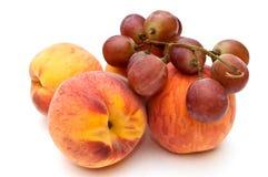 Pfirsiche und Trauben. Stockfotos