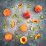 Pfirsiche und Trauben auf dunklem Hintergrund Geschnittene Pfirsiche auf dunkler Tabelle Fruchtkonzept Flache Lage, Draufsicht Stockbild