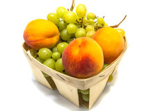 Pfirsiche und Trauben in einem Korb lokalisiert auf Weiß Stockbilder