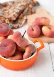 Pfirsichfeigen in einer keramischen Schüssel auf einem weißen Hintergrund Lizenzfreies Stockbild
