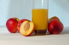Pfirsichsaftglas mit orange Apfel Stockbilder