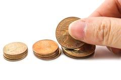 Pflücken Sie eine Münze von der Reihe mit der Hand Lizenzfreie Stockbilder