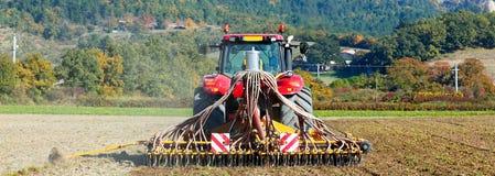 Pflügender schwerer Traktor während der Bearbeitung Lizenzfreie Stockfotografie