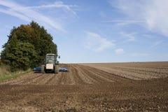 Pflügendes Feld des Traktors Stockfoto