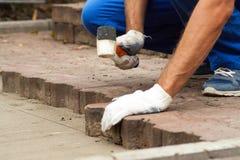 Pflastersteine auf den Stadtplatz legen, B?rgersteig reparierend stockfoto