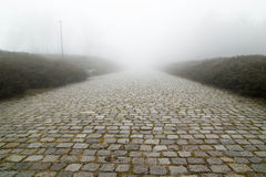 Pflastersteinstraße mit Nebel Stockfotos