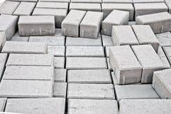 Pflasterung der grauen Steinblöcke der Bürgersteige Stockfotografie