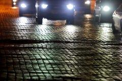 Pflasterung der Straße nachts durch das Licht von Autos Lizenzfreies Stockfoto