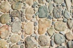 Pflasterung die Blöcke gemacht von den runden Steinen und vom konkreten Weg Stockfotos