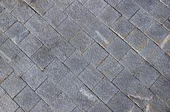 Pflasterung gemacht von den grauen Granitpflastersteinen Stockfotos