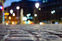 Pflasterung und unscharfes Stadtlicht während der Nachtzeit Stockbild