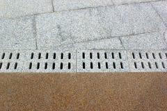 Pflasterung von Fliesen auf einem Bürgersteig mit Grundwasserentwässerungsabzugskanal Lizenzfreie Stockbilder
