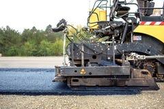 Pflasterungs-LKW, der frischen Asphalt auf die Baustelle, asphaltierend legt Lizenzfreies Stockbild