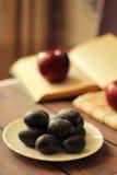 Pflaumen auf einer Platte und Äpfel mit hölzernem Hintergrund Lizenzfreie Stockbilder